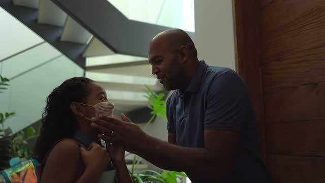 padre che regola la maschera protettiva delle figlie a casa prima di partire per la scuola - padre single video stock e b–roll