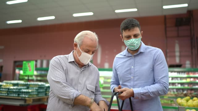 father an son buying with face mask at supermarket - new normal video stock e b–roll