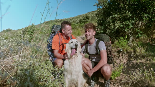 Father and Adult Son Having a Break with Their dog While Hiking in the Mediterranean coast
