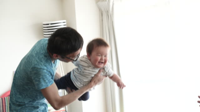 Father and baby boy having fun time in house. video