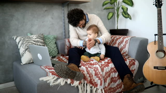 Padre y bebé niño viendo caricaturas en la computadora portátil - vídeo