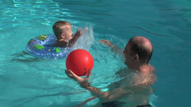 Father and baby daughter playing in the pool video