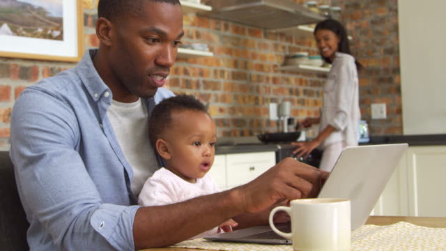 father and baby daughter use laptop as mother prepares meal - genitori video stock e b–roll