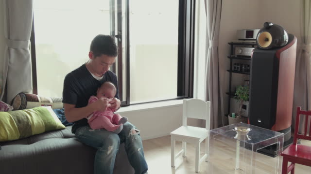 4 k 、父、赤ちゃんのリビングルーム。東京,日本 - 居間点の映像素材/bロール
