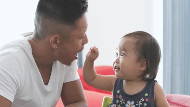 stockvideo's en b-roll-footage met vader en baby voorwenden om te eten. - video's van baby