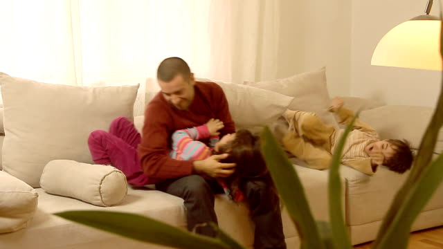 Father and children having fun while wrestling each other. Father and children playing on sofa and having fun while wrestling and tickling each other. wrestling stock videos & royalty-free footage
