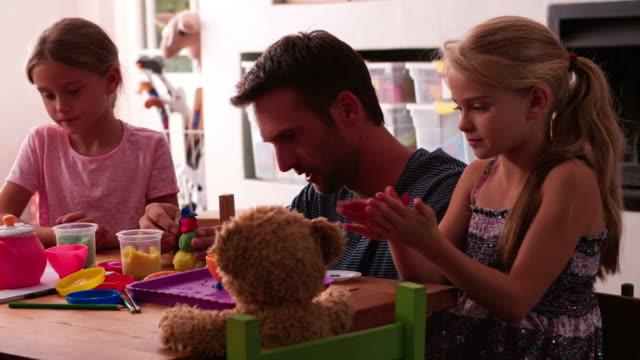 Padre jugando con niños y el modelado con arcilla en - vídeo