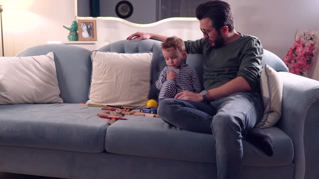 Father And Cute Baby Boy Sitting On Sofa At Home Playing Together On Toys