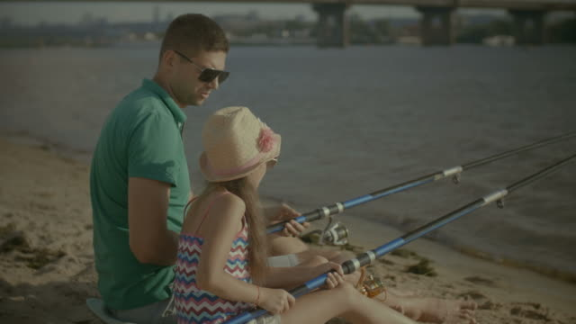 Father and cute girl fishing from shore on river video