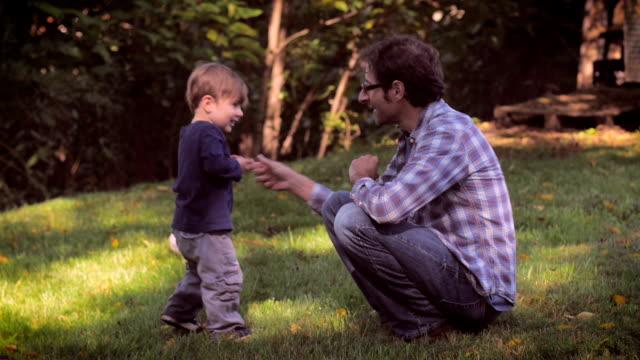 Un padre y linda niño pequeño hijo pasar tiempo juntos en la naturaleza en slomo al - vídeo