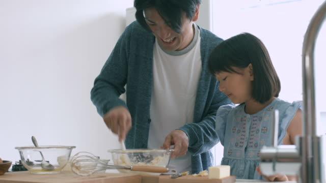 ojciec i córka pieczenia razem - piec przygotowywać jedzenie filmów i materiałów b-roll