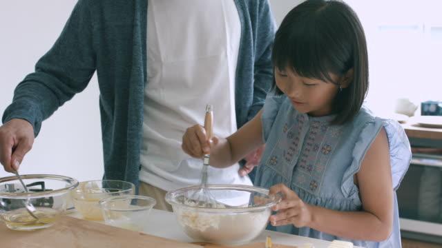 vídeos y material grabado en eventos de stock de padre e hija cocinar juntos - cocina doméstica