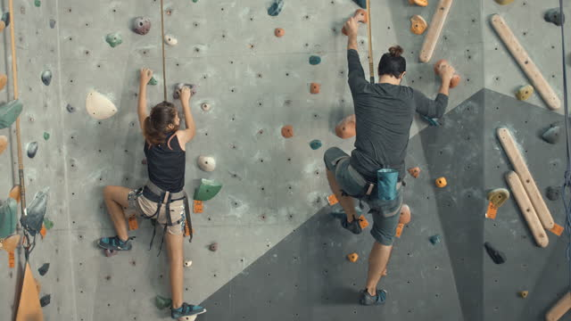 Father and daughter climbing in a climbing gym