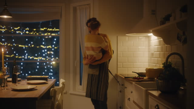 Father and Daughter Cooking and Having Dinner Together. Father Prepares Food, Little Girl Runs and Hugs Him, They Dance, Swirl. Festive Table in Stylish Kitchen Interior with Warm Light. Slow motion