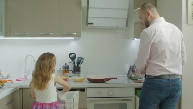 vídeos y material grabado en eventos de stock de padre e hija cocinando el desayuno en cocina - padre que se queda en casa
