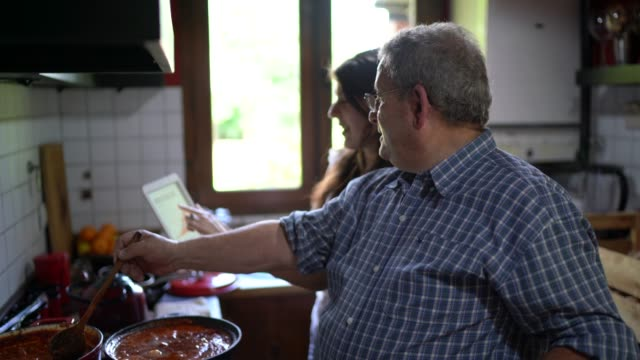 vídeos de stock e filmes b-roll de father and daughter cooking together and using digital tablet - sauce