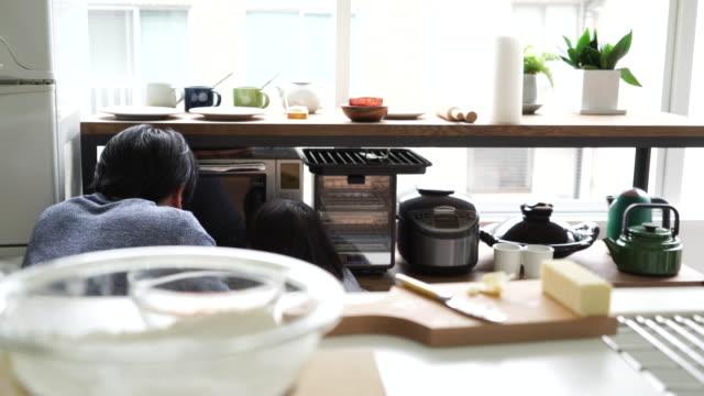 台所で一緒に料理する父と娘 - 電化製品点の映像素材/bロール