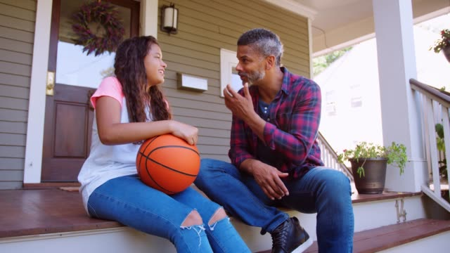 father and daughter discussing basketball on porch of home - genitori video stock e b–roll