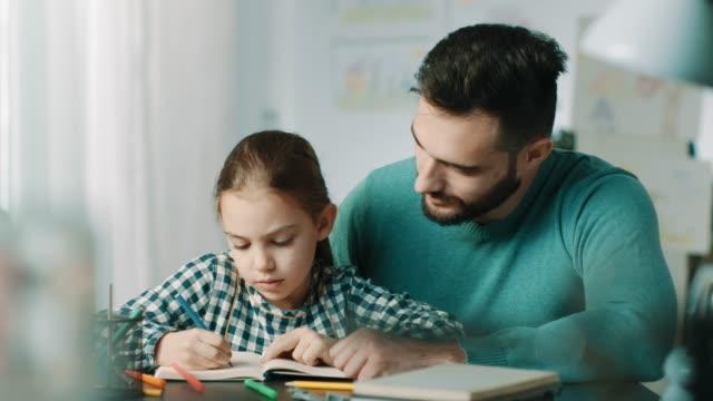 far och dotter göra läxor tillsammans - working from home bildbanksvideor och videomaterial från bakom kulisserna