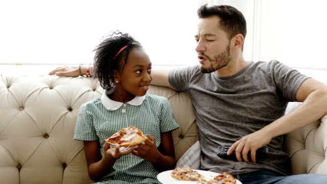 Father and daughter eating pizza and watching TV Transgender father with his daughter sitting on sofa and eating pizza while watching television at home transsexual stock videos & royalty-free footage