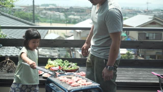 vidéos et rushes de père et fille en appréciant un barbecue sur la terrasse - seulement des japonais