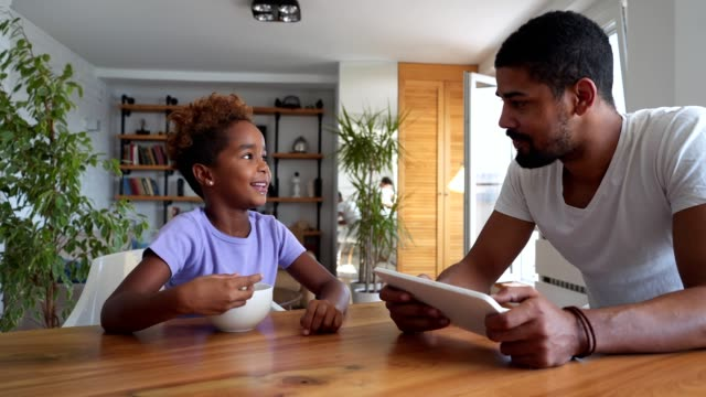 Padre e hija disfrutando de su tiempo juntos en la mesa de comedor - vídeo