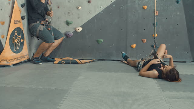 Father and daughter falling down from a climbing wall during training,Slow motion