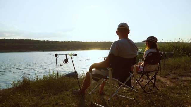 Father and daughter fishing on river bank at sunset video