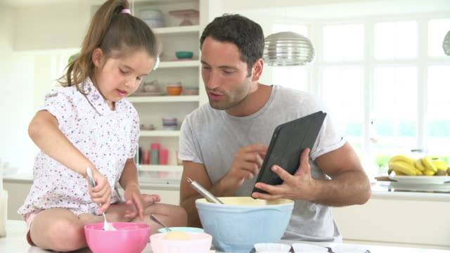 Father And Daughter Following Cake Recipe On Digital Tablet video