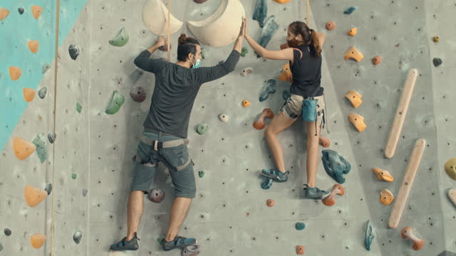 Father and daughter giving high five after a successful climb in a climbing gym,Slow motion