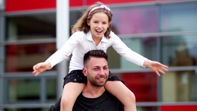 Father and daughter, happy family. The girl sits on the shoulders of the man, she laughs cheerfully and spreads her arms out to the sides video