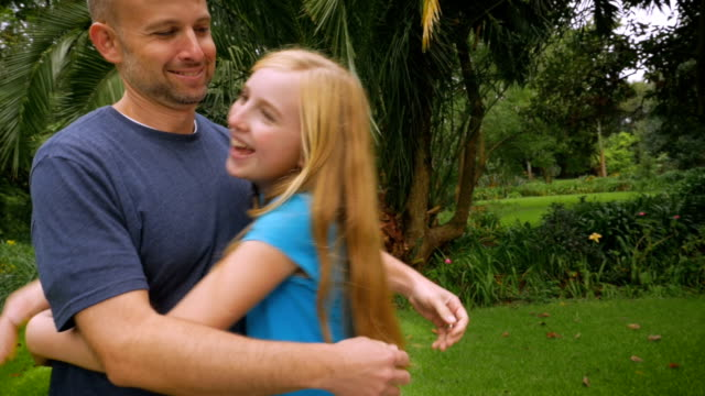 A father and daughter hug outside in nature - slowmo handheld video