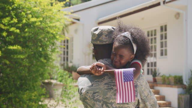 Father and daughter hugging each other Rear view of an African American man enjoying time in the garden, with his family, wearing military uniform, holding up his crying African American daughter holding a flag, embracing, on a sunny day, in slow motion military lifestyle stock videos & royalty-free footage
