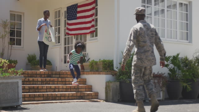 Father and daughter hugging each other Rear view of an African American man enjoying time in the garden, with his family, wearing military uniform, returning home, with his partner and daughter holding a banner, with his daughter running towards him, embracing, with american flag in the background, on a sunny day, in slow motion armed forces stock videos & royalty-free footage