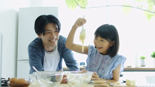 father and daughter making cake together - padre single video stock e b–roll