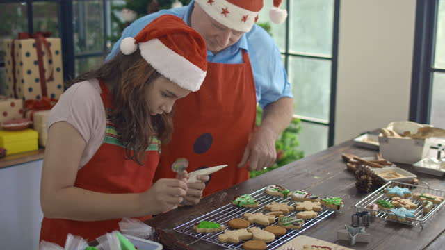Father and daughter making Christmas cookies together at kitchen counter