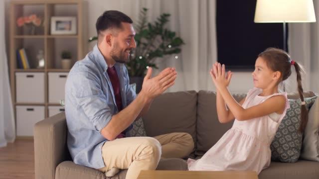 自宅で拍手ゲームをプレイしている父と娘 - 父の日点の映像素材/bロール