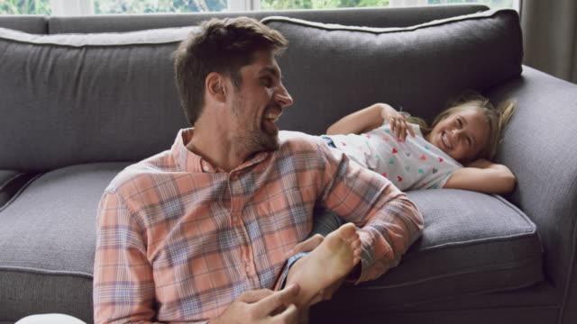 baba ve kızı ev 4k kanepede birlikte oynuyor - ultra yüksek çözünürlüklü televizon stok videoları ve detay görüntü çekimi