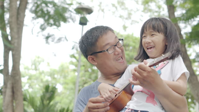 Father and daughter playing ukulele in the park video