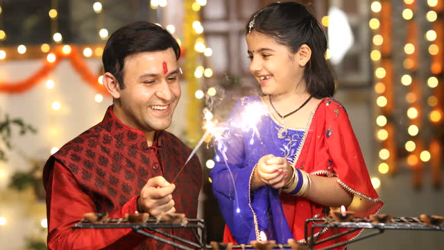 Father and daughter playing with crackers during Diwali festival