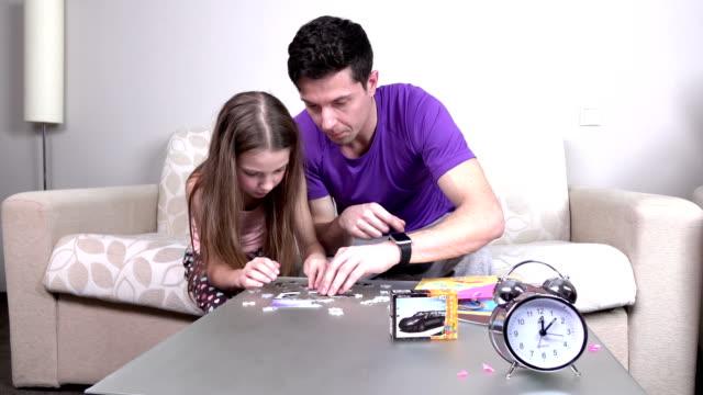 padre e figlia, giocando con puzzle sul tavolo - a forma di blocco video stock e b–roll