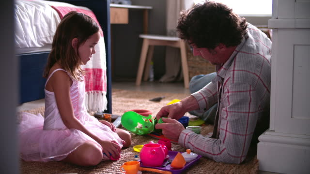 Father And Daughter Playing With Toys In Bedroom video