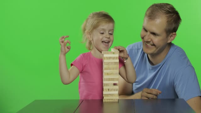vídeos de stock e filmes b-roll de father and daughter plays block removal game. pulls wooden blocks from tower - fundo oficina