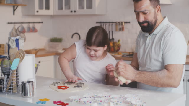 Father and daughter preparing cookies together video