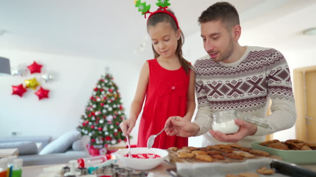 far och dotter förbereder pepparkakor isbildning för att dekorera sina julkakor - pepparkaka bildbanksvideor och videomaterial från bakom kulisserna