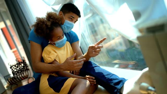 vidéos et rushes de père et descendant s'asseyant par une fenêtre pendant la quarantaine de coronavirus. - enfant masque