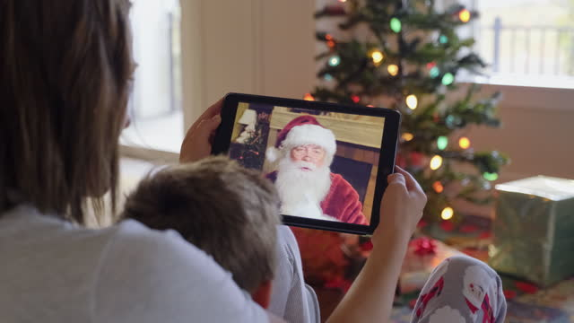 vídeos de stock e filmes b-roll de father and daughter talking to santa claus on a video call - pai natal