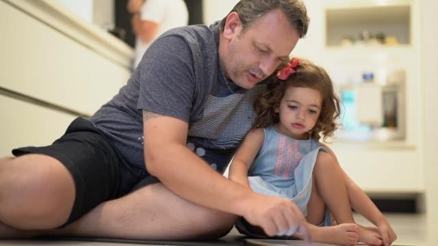 vidéos et rushes de père et fille utilisant la tablette numérique à la maison - enfant d'âge pré scolaire
