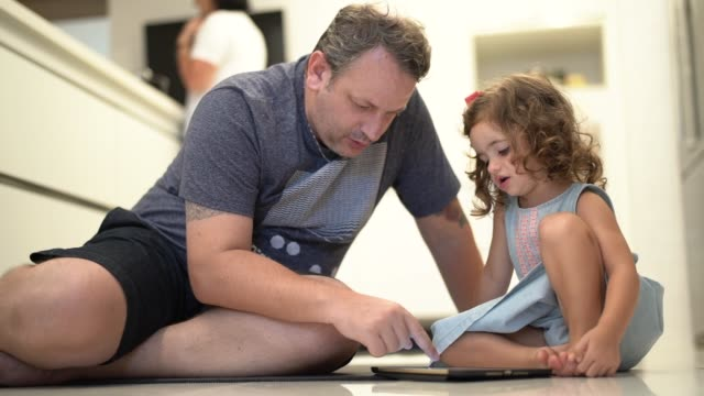 Father and daughter using digital tablet at home video