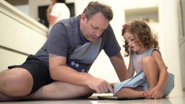 Padre e hija usando tableta digital en casa - vídeo